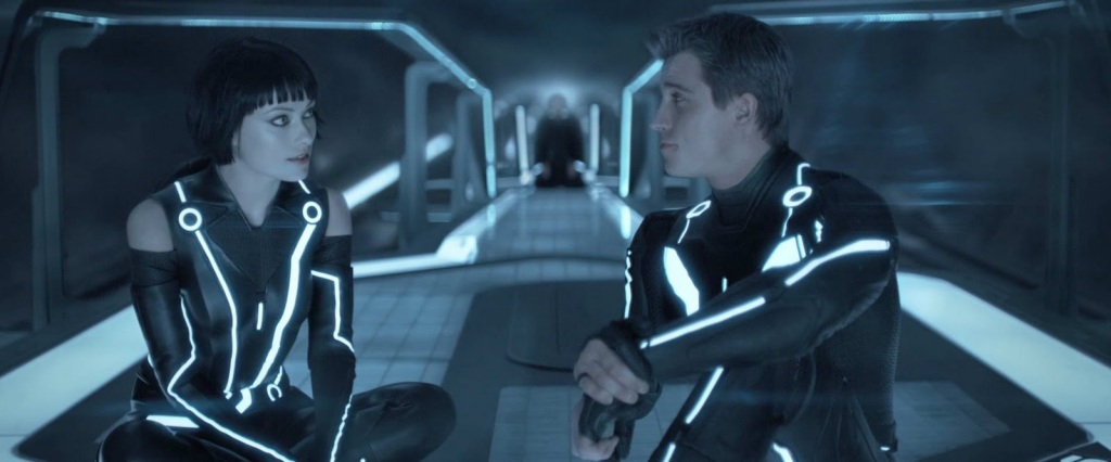 A women and a man, each wearing skin-tight suits laced with strips of blue neon lights, sit on a futuristic space deck whilst looking at each other. In the background out of focus is a figure in black clothing kneeling as if in prayer. From 'Tron: Legacy'