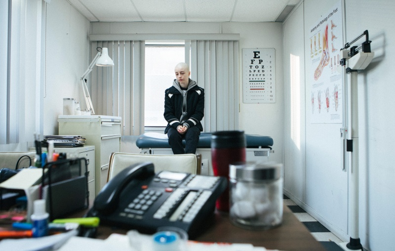 A bald, young woman is sitting in a doctor's office.