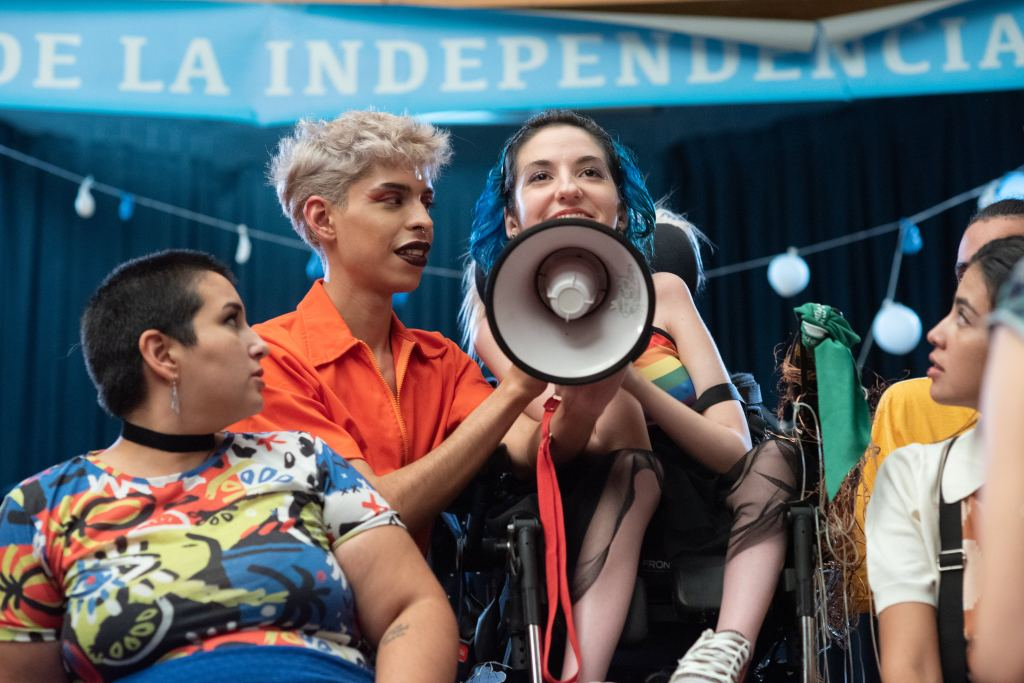 A young, female wheelchair user shouts into a megaphone which is held up by her friend.