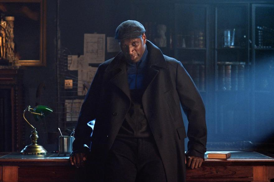 Omar Sy as Assane Diop, dressed in a big black coat and leaning against a desk.