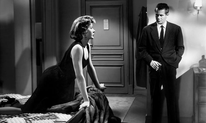 Dave Bannion (Glenn Ford) stands talking to Debby Marsh (Gloria Grahame).