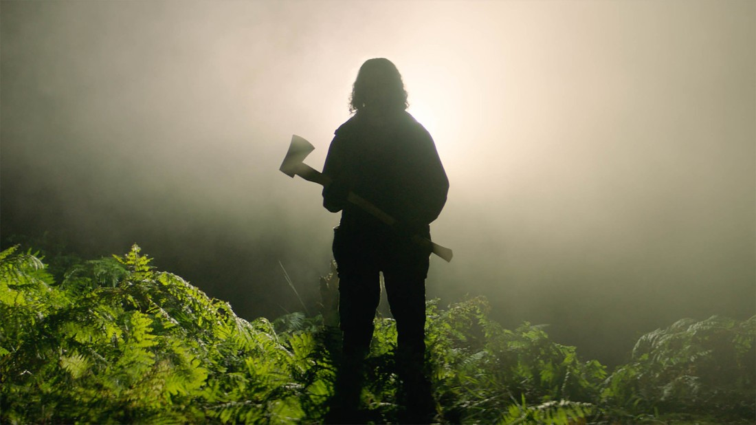 Image shows the silhouette of an axe wielding man in a misty forest.