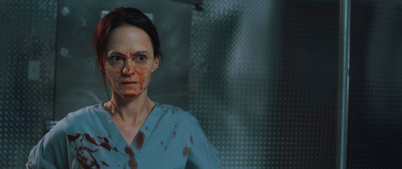 Angela Bettis in horror-comedy 12 Hour Shift. A woman in a light blue nurse uniform looks alarmed and annoyed, her gown and face are covered in blood. The background is a grey, bluish wall of an autopsy room.