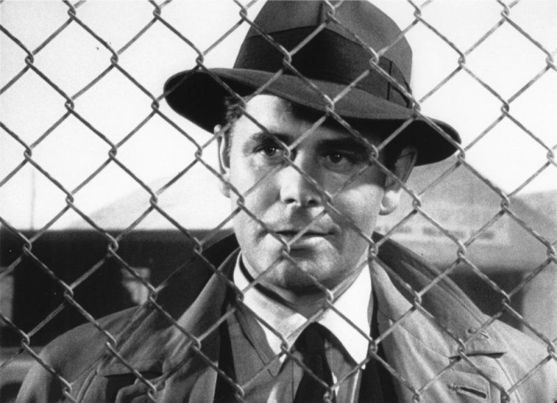Dave Bannion (Glenn Ford) stands behind metal fencing.