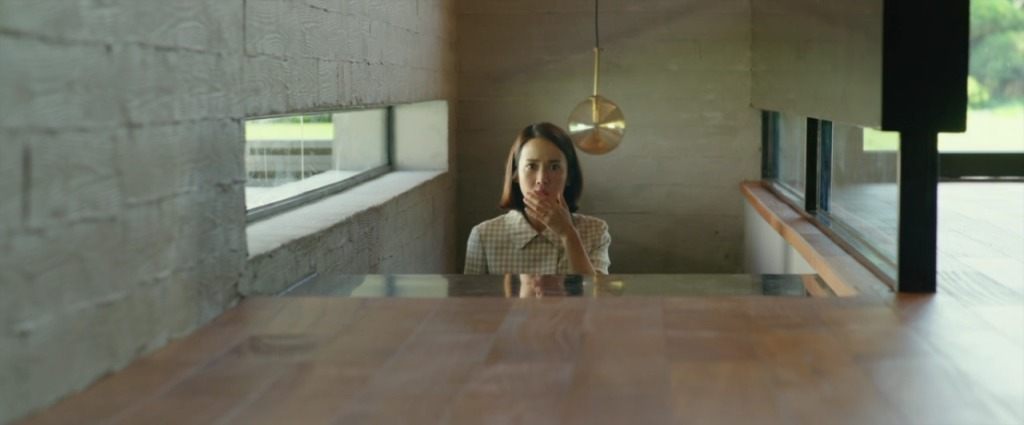 We see the top half of a woman wearing a bright white and yellow top as she makes her way up some stairs in a sleek, modern and minimalistic house with wooden flooring. Her hand is held over her mouth, shocked at something off screen.