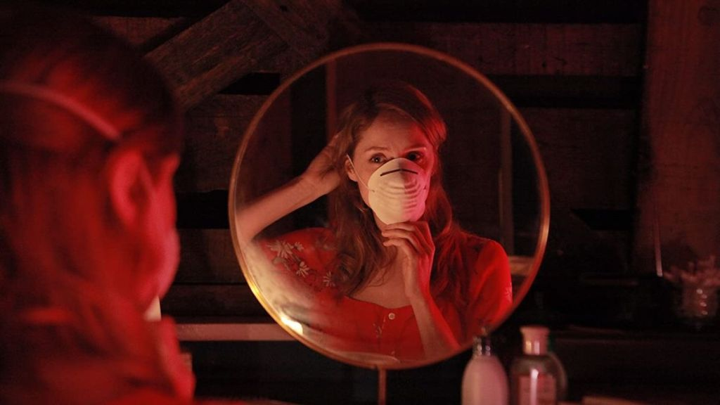 A circular mirror reveals a young woman pulling a respirator mask over her face, bathed in a dim, red light.