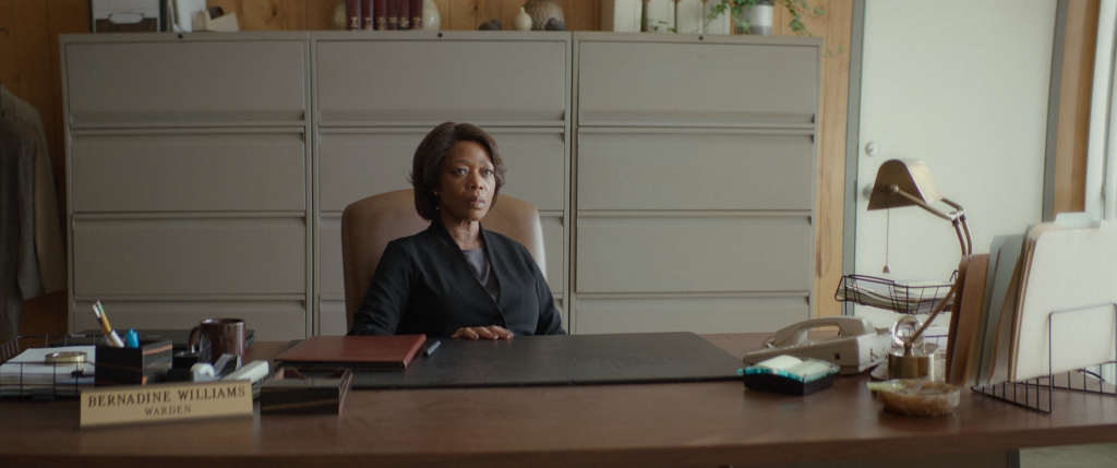 """A concerned looking woman sits at a large wooden desk adorned with folders, a phone, stationary and a name plaque saying """"Bernadine Williams- Warden"""""""