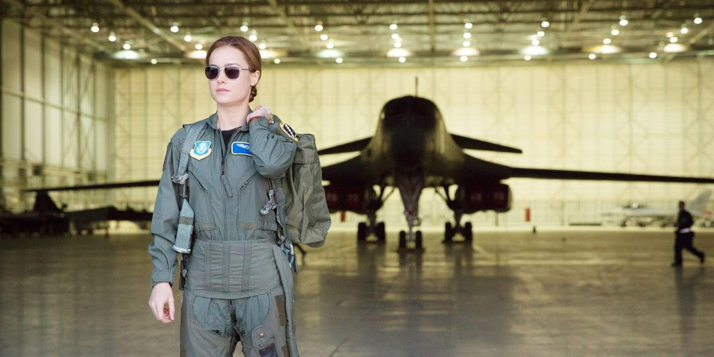 Carol Danvers (Brie Larson) stands in Air Force uniform in front of a military plane in Captain Marvel.
