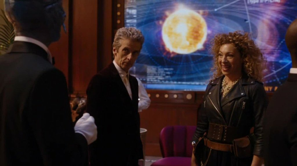 A smiling, leather jacketed River and a skeptical, suited Twelfth Doctor stand in front of an alien waiter in 'The Husbands of River Song'