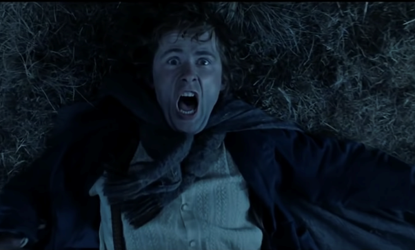 Still from the film The Lord of the Rings: The Two Towers. Merry, a white man wearing a scarf over his rustic shirt and jacket, is lying on the ground and screaming. The shot is a close-up bird's eye view.