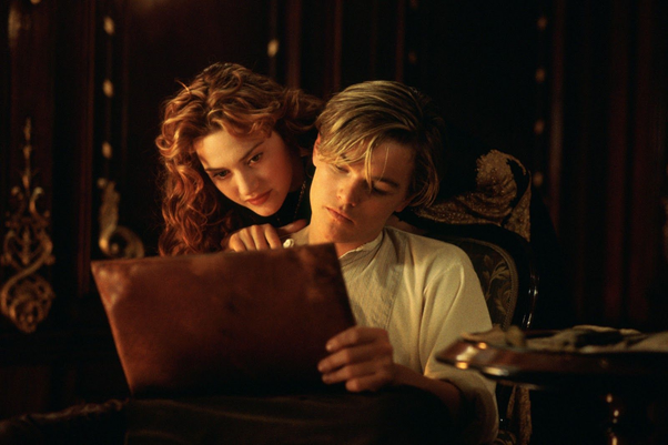 Still from the film Titanic. Rose, portrayed by a young Kate Winslet, is a white woman with long curly red hair. She's peering over the shoulder of Jack, portrayed by a young Leonardo DiCaprio, a white man with floppy blonde hair. Rose has her hand on Jack's shoulder, and she's looking at a sketch book that Jack is holding.