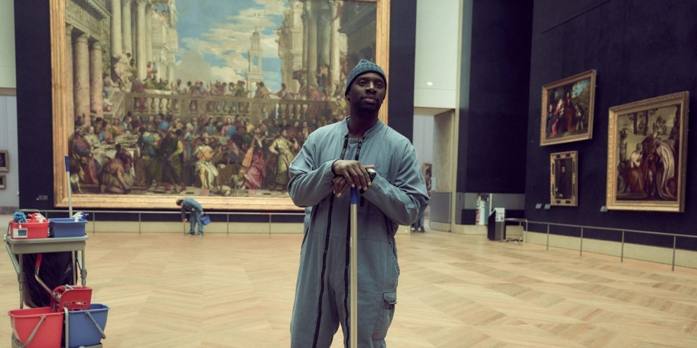 Omar Sy as Assane Diop, dressed as a janitor, surrounded by paintings in the Louvre.
