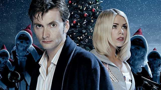 The Tenth Doctor, in pyjamas and a dressing gown, stands with Rose in front of robotic santas and a Christmas tree in this 'The Christmas Invasion' promo image