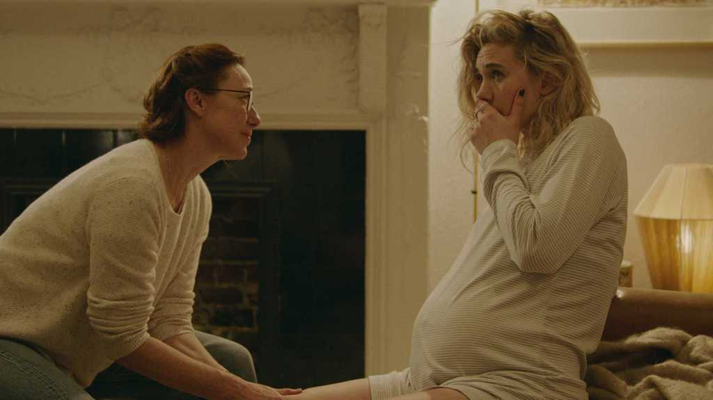 A pregnant woman sits on her bed and holds her hand to her face. Another woman sits with her.