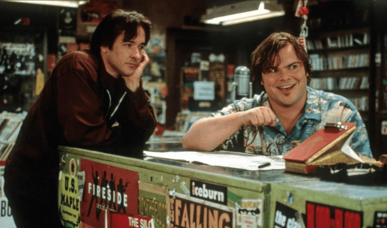 One man looks at another who is engaged in an enthusiastic conversation in a record shop.