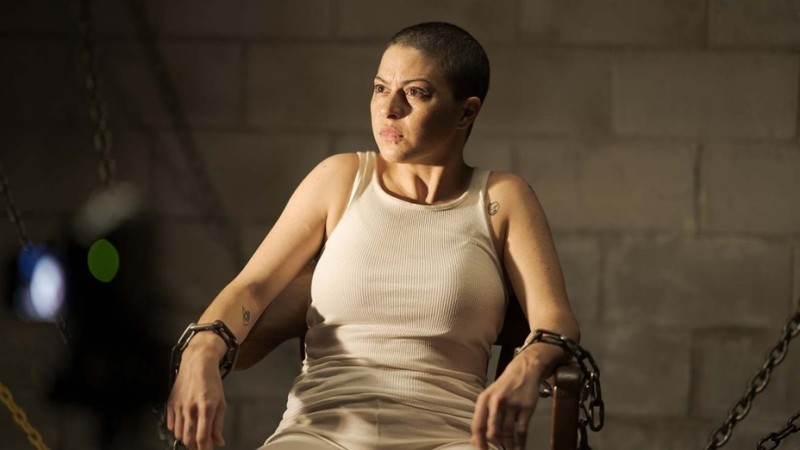 Image is from the TV Series, 'Search Party'. A young woman with a buzzed haircut and a few small tattoos is chained to a chair.