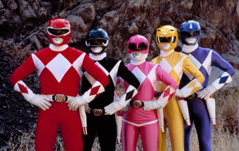 Image from the TV series Mighty Morphin' Power Rangers. All five rangers stand against a cliff face with their hands on their hips.