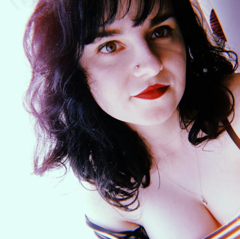 A selfie of Georgia Davis, who has dark curly hair and is wearing red lipstick.