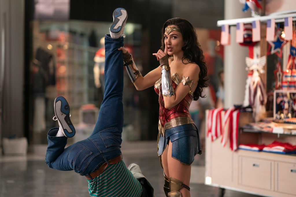 "Wonder Woman (Gal Gadot) holds a person up by the legs with one hand, with her finger to her lips in a ""shush"" gesture."