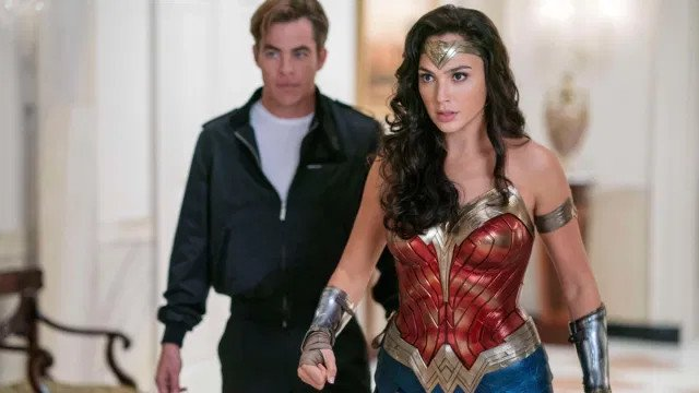 Wonder Woman (Gal Gadot) appears ready to fight in a hallway while Steve Trevor (Chris Pine) stands out of focus behind her.
