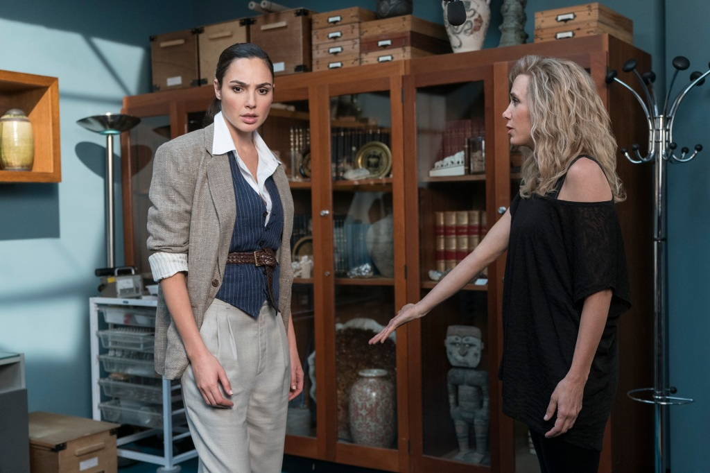 Diana Prince (Gal Gadot) stands in a museum office, looking at something Barbara Minerva (Kristen Wiig) is gesturing towards.