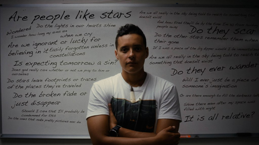 Jamaica Heolimeleikalani Osorio stands in front of a whiteboard filled with poetry.