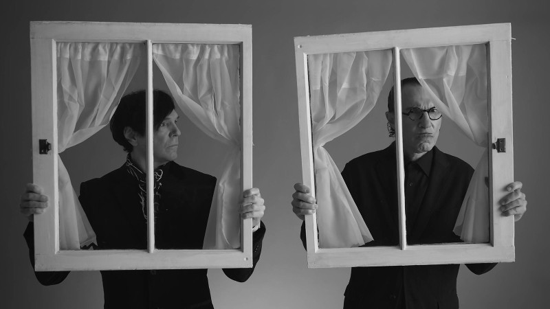 Image shows Ron and Russell Mael, the eponymous Sparks brothers, holding up window frames.