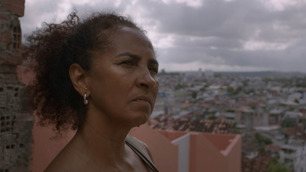 Marilene stares out across the city.