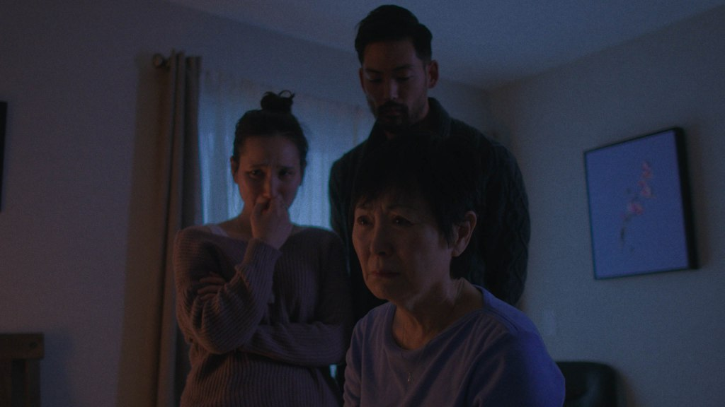 A family tearfully gathers around their dying father's bedside.