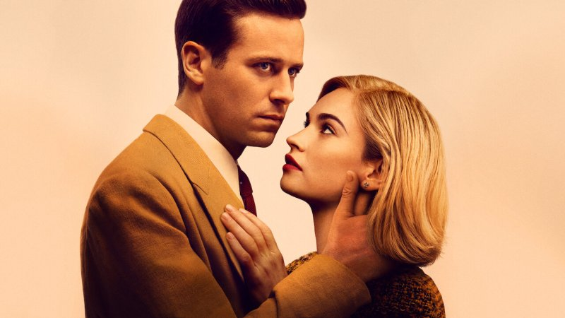 Promotional photograph of film stars Armie Hammer and Lily James in Rebecca (2020). They are holding one another but James is looking at Hammer whilst Hammer looks in the distance.