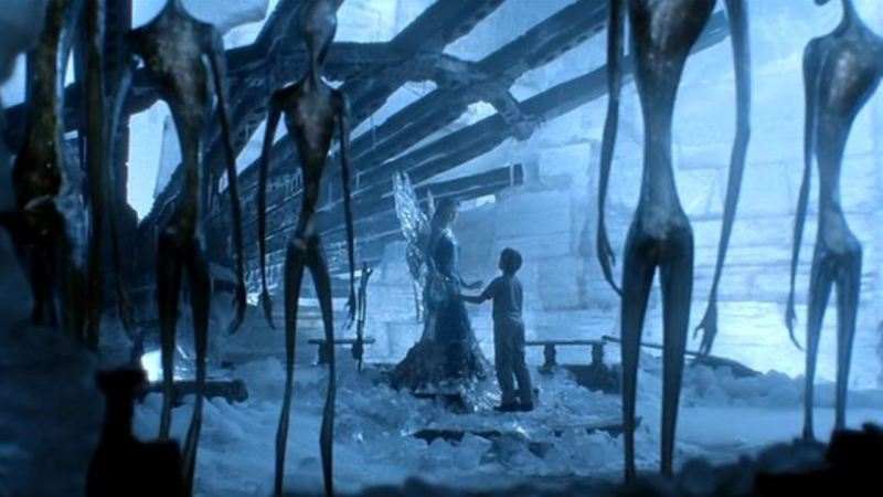 Image from the film 'AI: Artificial Intelligence'. Enshrouded by a blue atmosphere, a fairy holds hands with a child in an icy cave. Long, thin, humanoid figures watch over them.