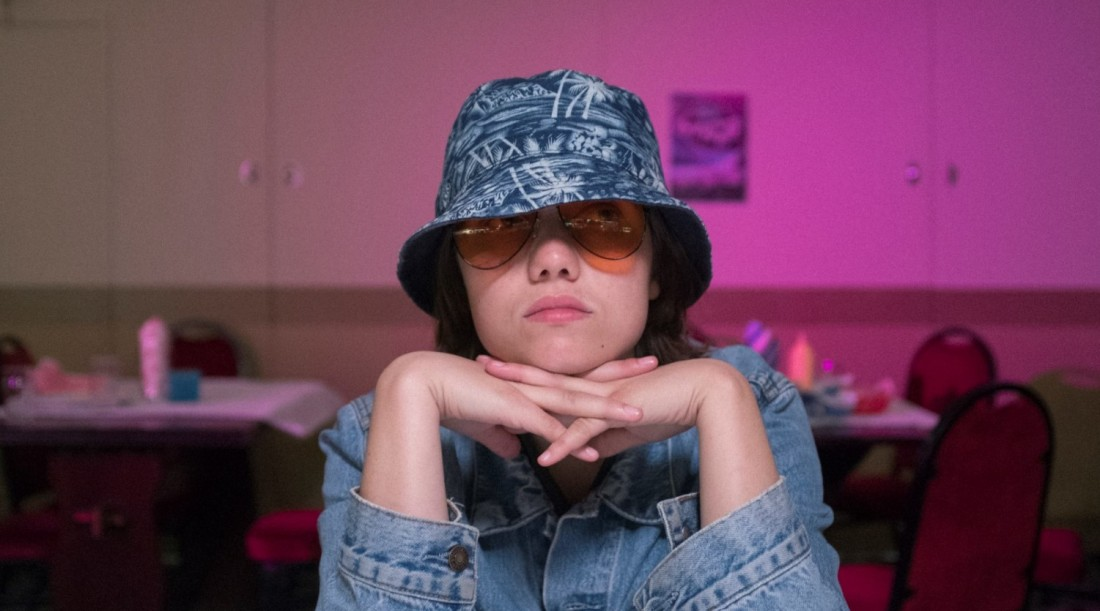 Image from the film Sweetheart. A young person rests their head in their folded hands. They hide their features behind a pair of orange sunglasses and a blue bucket hat.