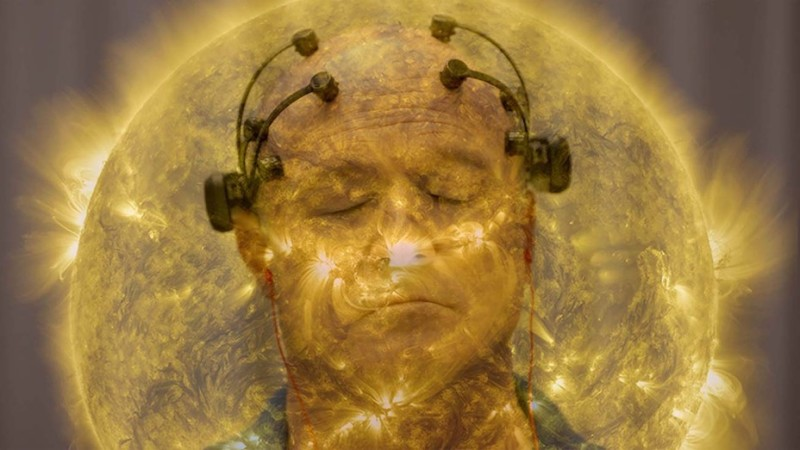 The image from the documentary All Light Everywhere. It shows two separate images layered over each other. The first a yellow hued image of the sun, and the second a man with scientific equipment attached to his head.