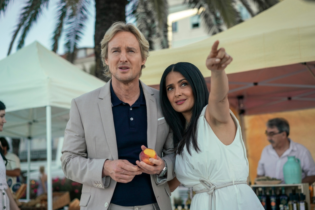A still from the sci-fi film Bliss. The background is a sunny seaside resort with a blurred palm tree behind a confused man and happy woman. The man has blonde hair and is played by Owen Wilson, dressed in a grey suit jacket with a black shirt. He's holding a half-eaten peach. The woman has long black hair, dressed in a white gown, and is played by Salma Hayek. She's pointing proudly into the distance at something we cannot see.