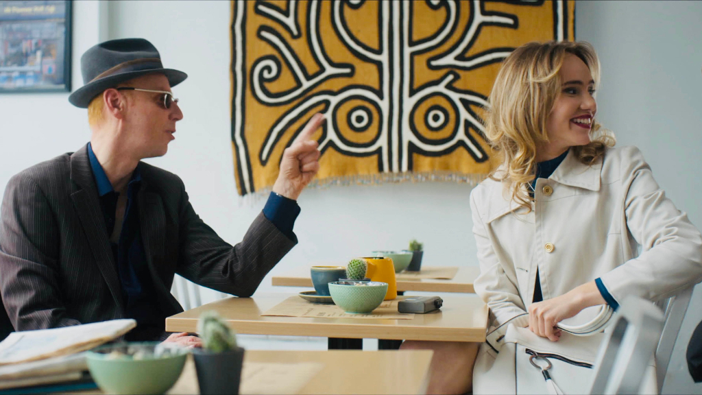 Image from the film Creation Stories. A man and woman sit at a coffee table, both are looking at something to their right that seems to be funny.