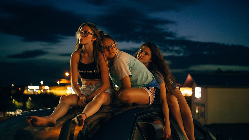 Image is from the documentary 'Cusp'. Three girls sit on top of a car roof at night. One is blowing smoke from her mouth with the other two lean on one another, looking directly at the camera.