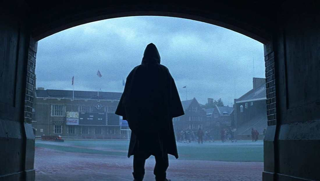 Image is from the film 'Unbreakable'. Under an archway, a hooded figure stands and watches a group of athletes run track in the pouring rain.