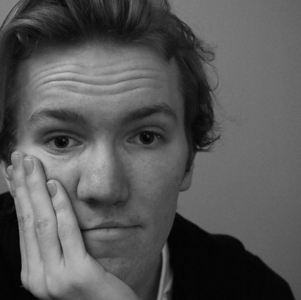 A black and white selfie of Derek Sharp, who holds his head in his hand as he looks to the camera.