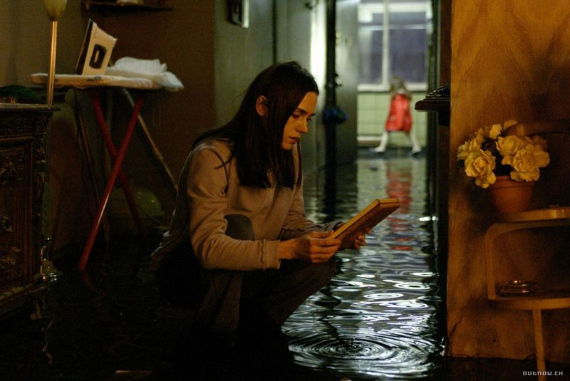 Image from the film 'Dark Water'. A young woman kneels down in a corridor that is completed flooded, holding a book. At the end of the corridor, a little girl wearing a red coat walks past.