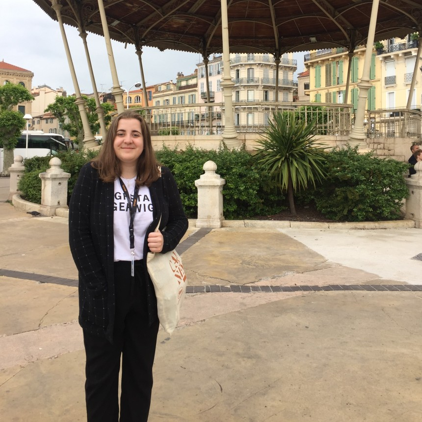 Image of Emily Maskell, who smiles at the camera while standing in front of a pavilion.