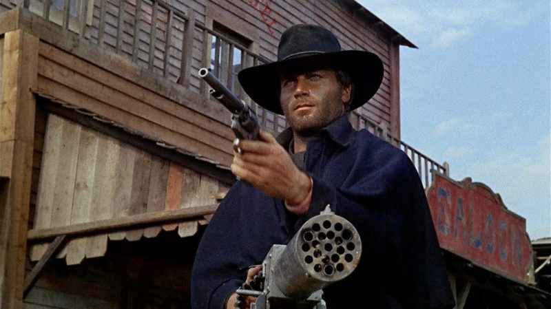 Django (Franco Nero) holds a revolver in one hand and a machine gun in the other.