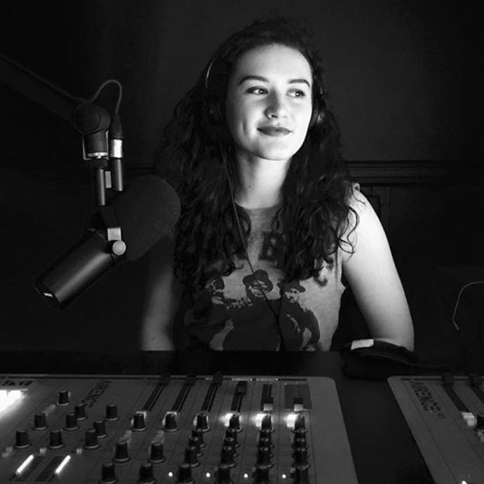 A black and white image of Georgia Carroll, who is sat at a radio desk with headphones on.