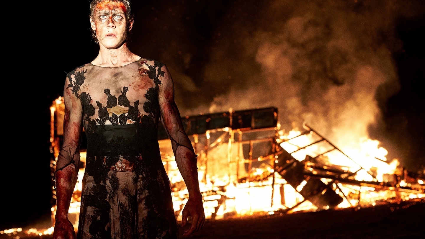 Ned Kelly (George Mackay) stands bloodied in his Rorschach-esque dress. Behind him, a building is burning to the ground.