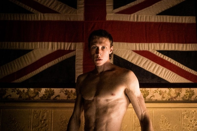 Image is from the film 'True History of the Kelly Gang.' A young man stands shirtless in front of a large union jack flag, which is hung on the wall behind him. He is looking directly at the camera.
