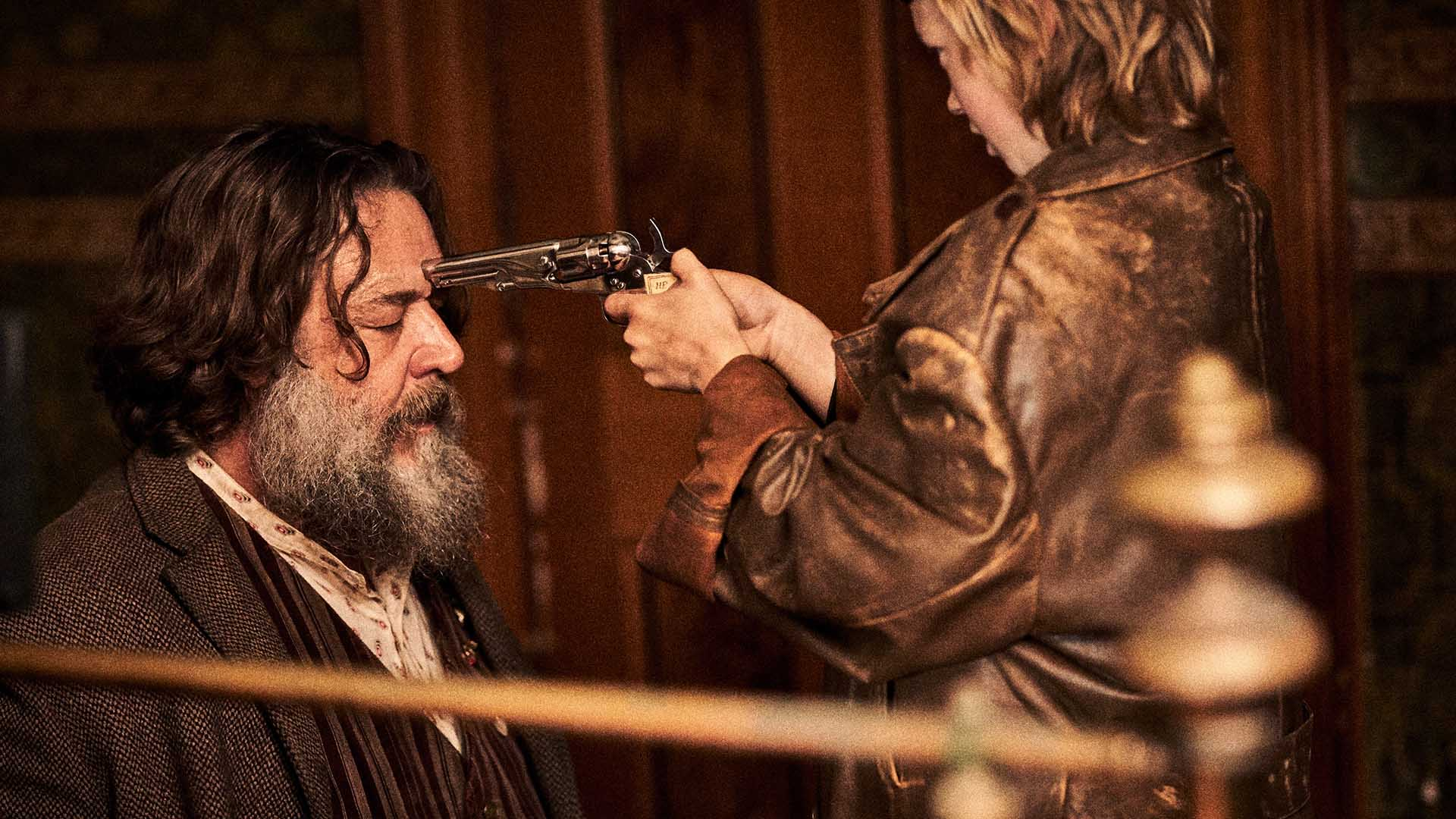 Harry Power (Russell Crowe) at the mercy of a young Ned Kelly (Orlando Schwerdt), who is pointing a gun to his head.