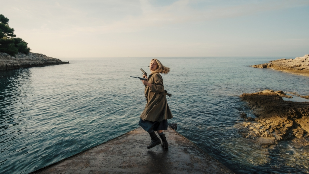 Mia Goth as Marsha with a  cigarette in her mouth, guns in both her hands. she is mid-spin towards the camera with a long coat and standing on a rock with an ocean behind her