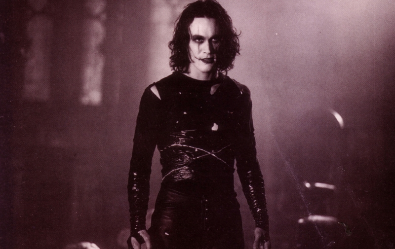 Brandon Lee in 1994 film The Crow. A smoky, grungy, dark brown backdrop, with Lee in centre frame. He's dressed all in black, black curly hair, and black leather, torn at the shoulder. His face is coated with white makeup, black lines running vertically through his eyes and at the corners of his mouth into a wicked smile.