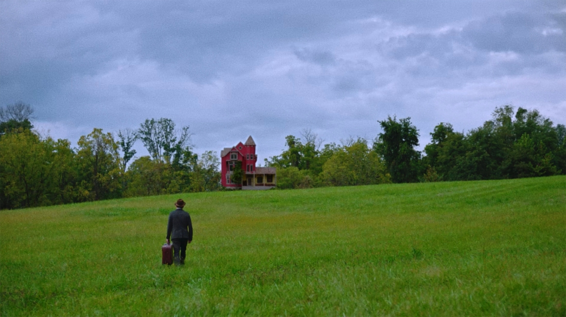 Image is from the film Strawberry Mansion. A man in a suit stands in a field, holding a briefcase. He looks towards a red house in the distance.