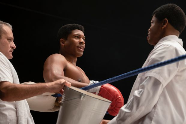 Eli Goree as Cassius Clay stands in the corner of a boxing ring, talking to two men who are his trainers/coaches.