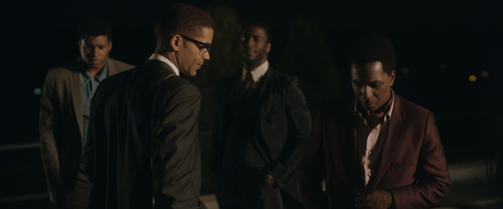 From left to right: Cassius Clay, Malcolm X, Jim Brown, and Sam Cooke. The men are in conversation, standing outside on a rooftop.